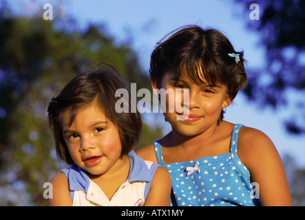 Portrait of 3 year old and 8 year old Hispanic sisters - Stock Image