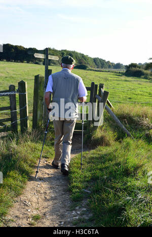 Walker about to pass through the kissing gate and walk across the field at Dell Quay, Chichester Harbour, West Sussex - Stock Image