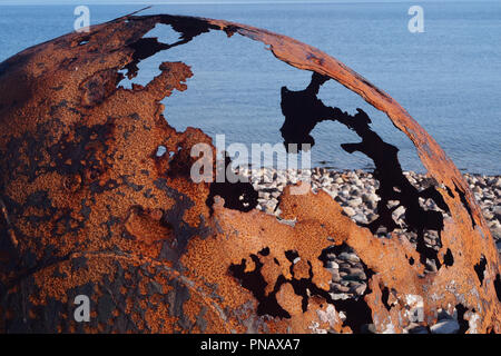 A view of broken, large, discarded iron sea floats on Badentarbat beach, Scotland with the sea in the background - Stock Image