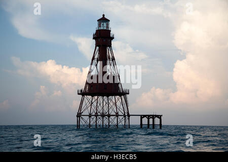 The rising sun at dawn tints the building summer clouds behind the skeletal tower of Florida's American Shoal - Stock Image