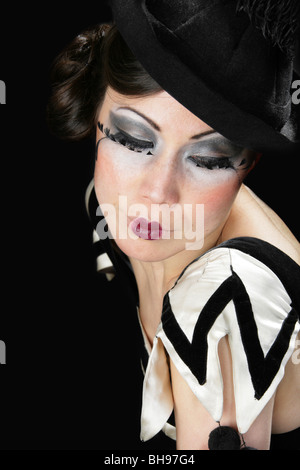 Young Woman Dressed in a Black and White Clown Outfit and Black Hat with Feather Eyelashes - Stock Image
