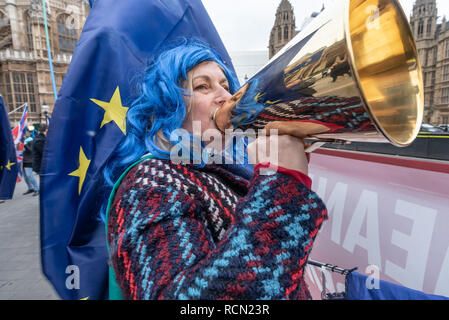 London, UK. 15th January 2019. A woman with SODEM shouts though a metal megaphone. Groups against leaving the EU, including SODEM, Movement for Justice and In Limbo and Brexiteers Leave Means Leave and others protest opposite Parliament as Theresa May's Brexit deal was being debated.  While the two groups mainly kept apart, a small group, some in yellow jackets came to shout insults at pro-EU campaigners, while police tried to keep the two groups separate. Credit: Peter Marshall/Alamy Live News - Stock Image