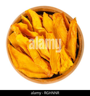 Dried mango strips in wooden bowl. Sliced, dehydrated mangoes. Juicy tropical stone fruit with yellow and orange color. Mangifera. - Stock Image