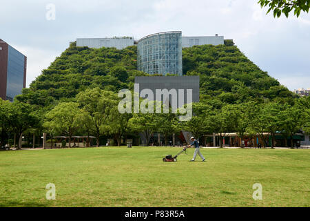 A man mows the lawn in Tenjin Central Park in front of the eco-friendly ACROS building in Fukuoka, Japan. - Stock Image