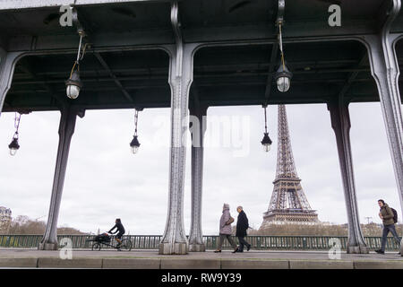 People passing along the Bir Hakeim bridge with a view of the Eiffel Tower in Paris, France. - Stock Image