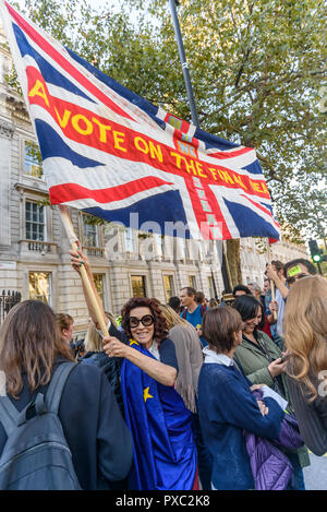 London, UK. 20th October 2018. A woman holds a Union Jack with the message 'A vote on the Final Deal' at the end of the People's Vote March calling for a vote to give the final say on the Brexit deal or failure to get a deal. They say the new evidence which has come out since the referendum makes it essential to get a new mandate from the people to leave the EU. With so many on the march the crowding meant many failed to reach Parliament Square and came to a halt in Whitehall. Peter Marshall/Alamy Live News - Stock Image