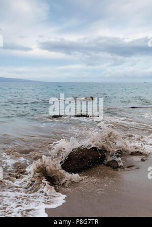 Wave breaks over a small rock at a beach on the west coast of Maui - Stock Image