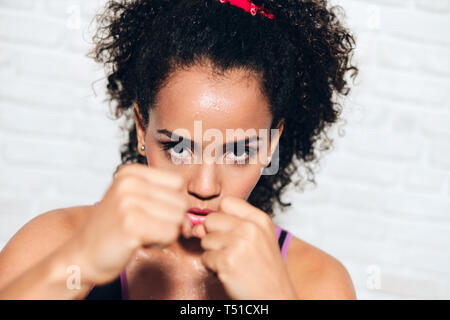 African american girl training in fitness club, gym, doing sport activity. Pretty young woman working out, fighting, boxing, exercising for self-defen - Stock Image