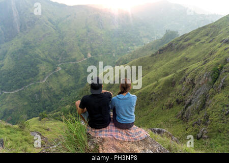 Couple travelers Man and Woman sitting on cliff, relaxing. Mountains aerial view - Stock Image