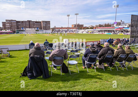 Hove Sussex, UK. 05th Apr, 2019. Spectators watch Sussex v Leicestershire in the Specasavers County Championship Division Two match at the 1st Central County Ground in Hove on a sunny but cool first morning of the season Credit: Simon Dack/Alamy Live News - Stock Image
