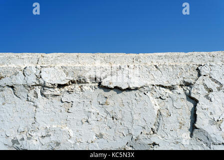 White cement wall with flaking paint and a blue summer sky with copy space area for construction ideas - Stock Image