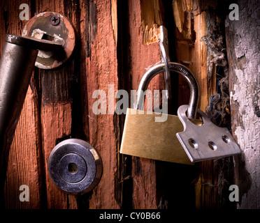 Broken padlock on a door - Stock Image