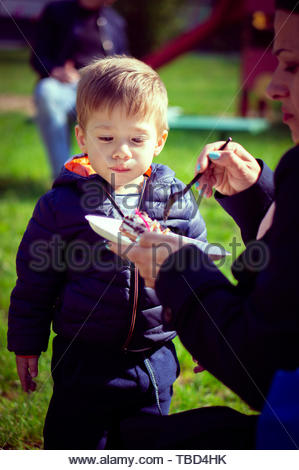 Small boy eating a cake from a paper plate given - Stock Image