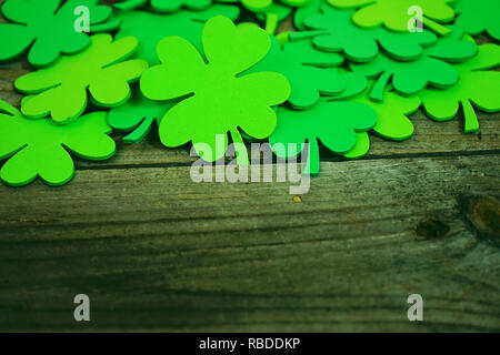 Beautiful close-up of a pile of green shamrocks or feast clovers over wooden tables that remind Saint Patrick's Day or lucky with space - Stock Image