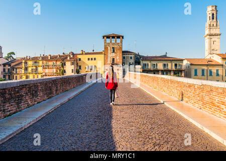 Woman walking along the Ponte Pietra (Stone Bridge). Verona, Veneto, Italy - Stock Image
