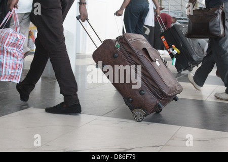 Passengers rushing to catch their flights in an early morning rush at the airport. - Stock Image