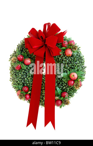 Christmas wreath with red velvet bow isolated on a white background - Stock Image