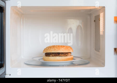 Unappealing microwavable hamburger on a plate in a microwave oven - Stock Image