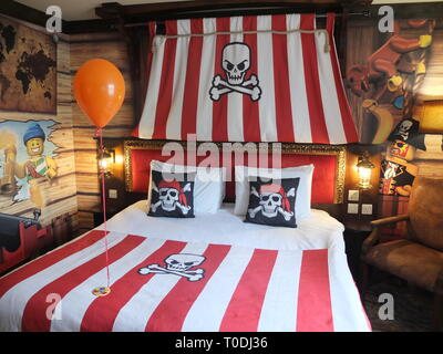 Adults double bed and décor in Premium Pirate Rooms at the hotel at LEGOLAND Windsor Resort UK with welcoming balloon and badge for child's birthday - Stock Image