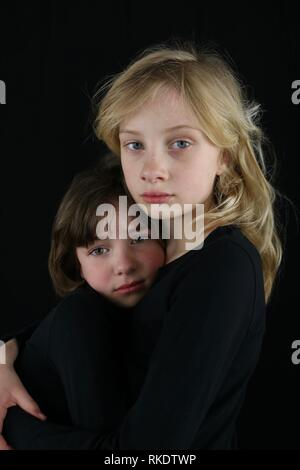 Grieving children holding onto each other - Stock Image