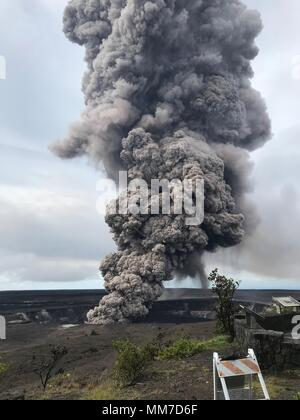 An ash column rises from the Overlook crater at the summit of Kilauea volcano believed to have been triggered by a rockfall from the steep walls of crater May 9, 2018 in Leilani Estates, Hawaii. The recent eruption continues destroying homes, forcing evacuations and spewing lava and poison gas on the Big Island of Hawaii. - Stock Image