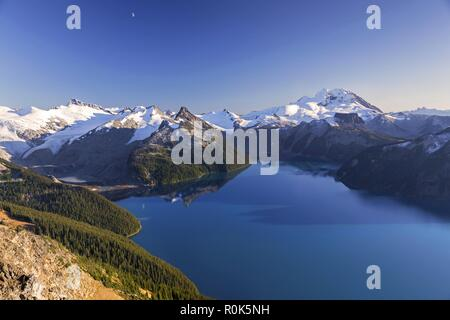 Scenic Landscape View of Blue Garibaldi Lake and Distant Snowcapped Coast Mountains in Sea to Sky Corridor between Squamish and Whistler, BC Canada - Stock Image
