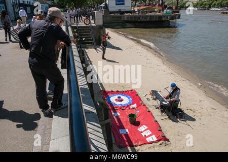 Man playing keyboard during summer on 'beach' at Gabriels Wharf alongside river Thames, London, UK - Stock Image