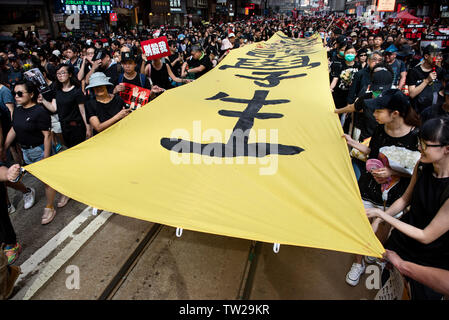 Protester carry a large banner during the mass rally. Nearly two million people joined the demonstration in another round of protest demanding the Hong Kong government to withdraw the extradition bill.Despite the Chief Executive Carrie Lam's attempt to ease the heightened tension by agreeing to suspend the controversial bill, close to 2 million people participated in Sunday's rally, according to the organizers. The protesters called for the withdrawal of the controversial extradition bill, the release and non-prosecution of the people arrested due to the cause, investigation of whether excessi - Stock Image