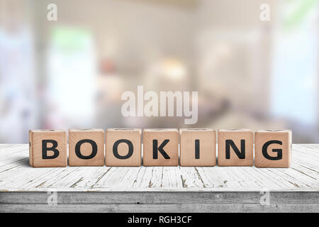 Booking sign on a wooden desk in a room with a bright blurry background - Stock Image