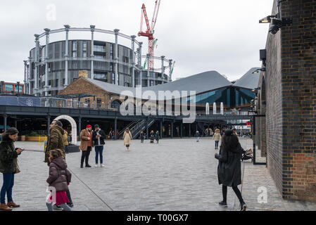 People at Coal Drops Yard, a refurbished area of Victorian buildings converted into shops, restaurants and leisure facilities, Kings Cross, London - Stock Image