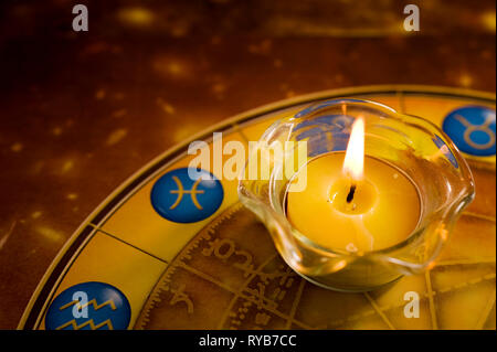 candle and astrology wheel - Stock Image
