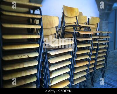 Piles of stacking chairs unsused before an event - Stock Image