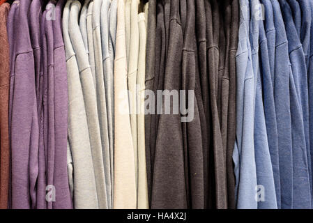 Brightly colored mens crisp and clean formal shirts on display in a shop interior - Stock Image