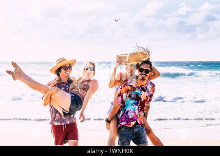 Cheerful people having fun in summer holiday vacation - group of young millennial tourists langh at the beach - men carrying woman on back and front - - Stock Image