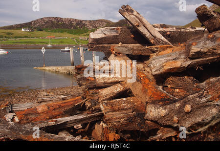 A view looking at part of Old Dornie harbour area, Polbain,Scotland with the remains of a timber boat/ship dominating the foreground - Stock Image
