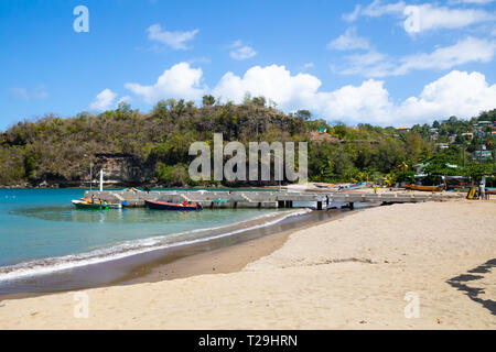 A view across a beach with boats moored up in St Lucia, The Caribbean - Stock Image