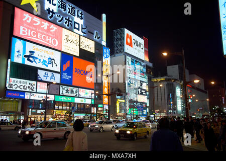 Detail of neon signs in the Susukino area at night in Sapporo, Hokkaido, Japan, with street traffic and  pedestrians at the dark bottom of the image. - Stock Image