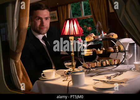 Handsome man in black suit sitting in vintage train carriage enjoying afternoon tea with cakes, sandwiches and tea - Stock Image