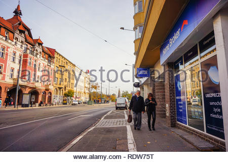 Poznan, Poland - November 1, 2018: Man and woman passing a Home Broker insurance office in the city center. - Stock Image