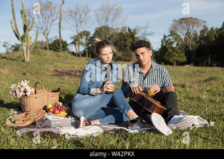 Man and woman drink juice while they enjoy their picnic and play the guitar - Stock Image