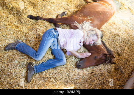 Iberian Sport Horse. Woman and bay foal resting together in a stable. Germany - Stock Image