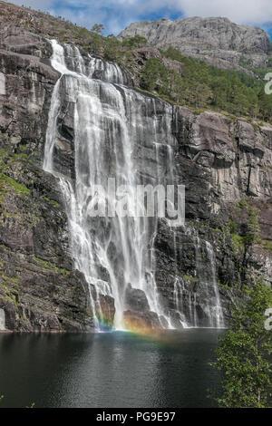 Norwegian scenic nature with waterfall and rainbow. - Stock Image