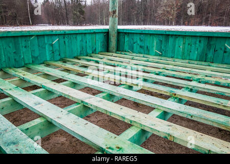 European bison and forest game new empty feeding rack in Bialowieza, Poland, partly snow, green hayrack, cloudy winter day - Stock Image