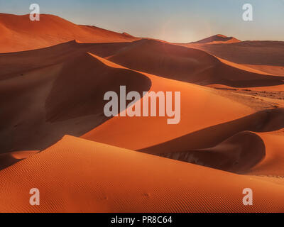 Sun rising over the curves, lines, and shadows of the red sand dunes of Namib Desert, Namibia. - Stock Image