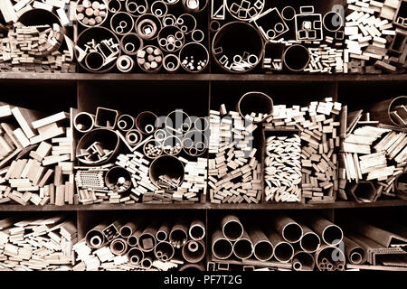 Bars, tubes of various sizes and shapes on shelves - Stock Image