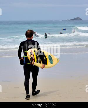 A man carrying a surfboard walking towards the sea,Sennen Cove,Cornwall,England,UK - Stock Image