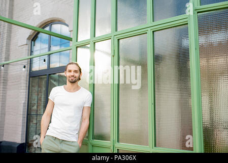 Portrait of a handsome smiling man in white t-shirt standing near the green wall outdoors - Stock Image