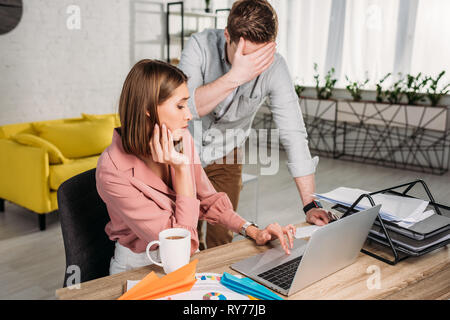 man standing and covering eyes near tired girlfriend sitting and looking at laptop - Stock Image