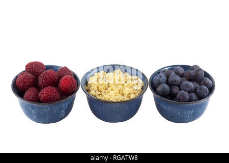 Small bowls of raspberries, cooked quinoa and blueberries. - Stock Image