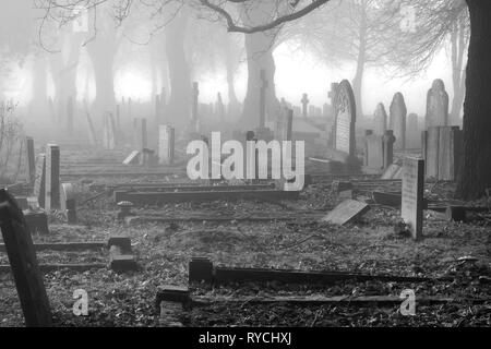 Black and white photo of a graveyard in the mist, there are around one hundred graves with headstones that are close together in the distance are a li - Stock Image